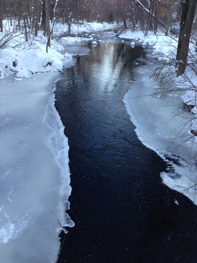 Beneath the ice, a sparkling, flowing stream.